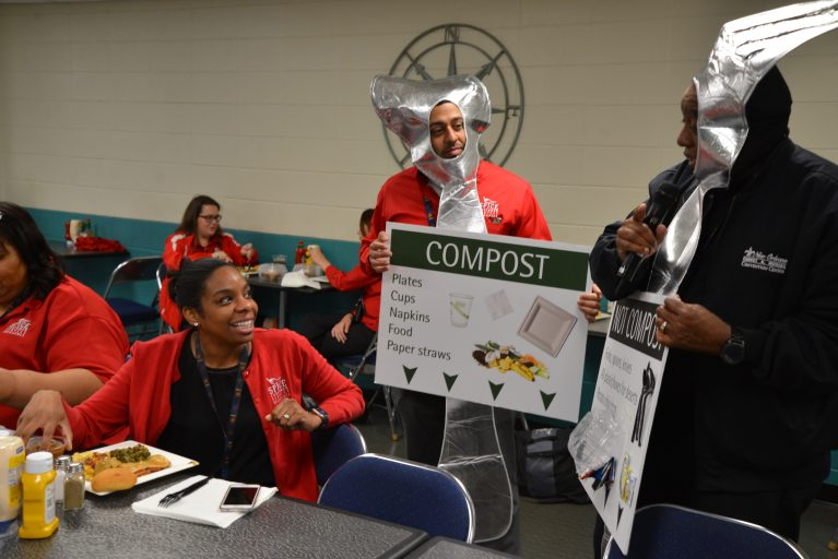 Jade Simmons, Financial Operations Manager, listens to a presentation on how to properly dispose of lunch waste from Erik Gonzales, Assistant Director of Event Operations, (Center) and Joe Young, Chief Engineer, (Right) during the Employee Education Event